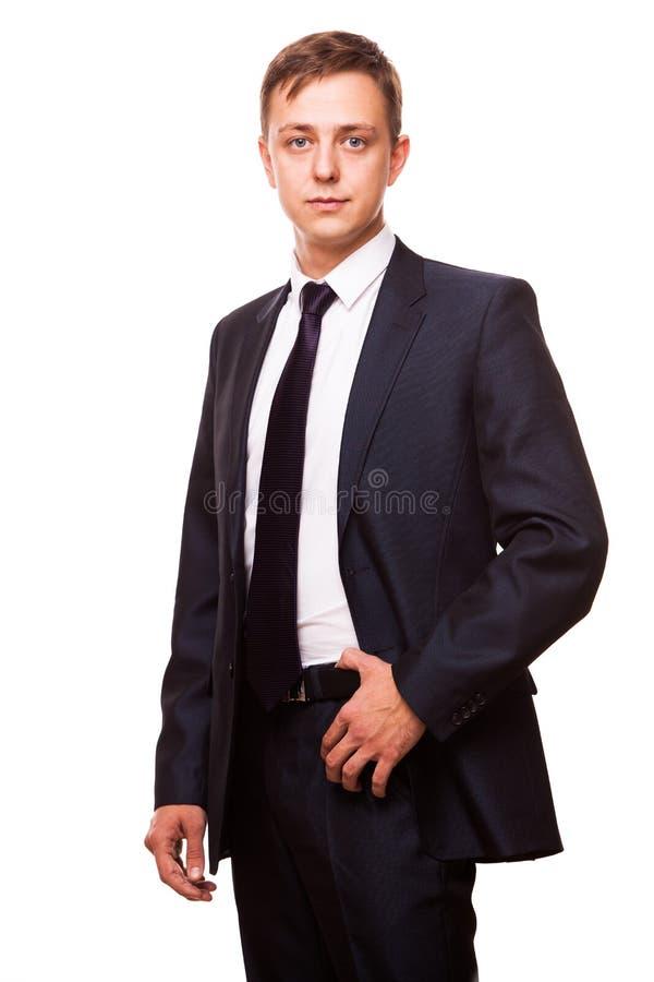Den unga stiliga affärsmannen i svart dräkt är den stående raksträckan, ståenden som isoleras på vit bakgrund arkivfoton