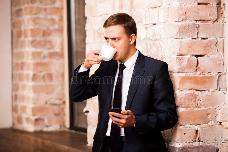 Den unga stiliga affärsmannen i svart dräkt dricker kaffe och surfar i telefonen nära tegelstenväggen royaltyfri fotografi