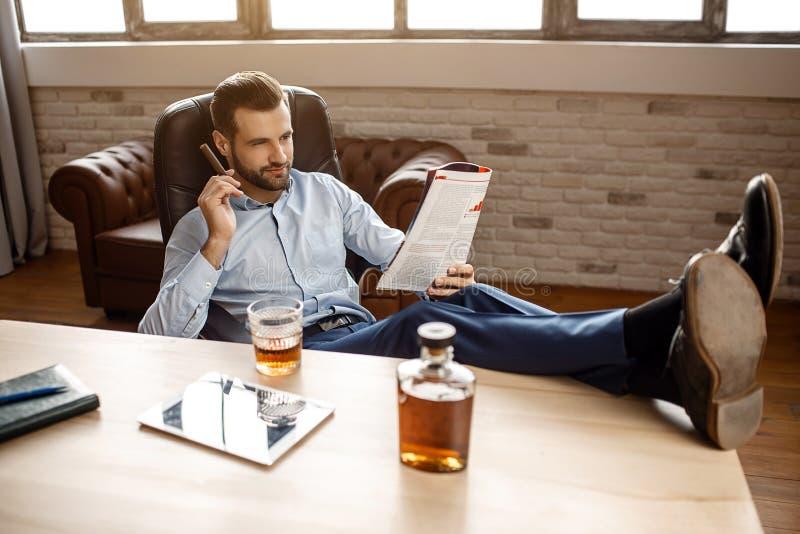 Den unga stiliga affärsmannen sitter på stol och den lästa tidskriften i hans eget kontor Han rymmer cigarren i hand och ben på t arkivfoto