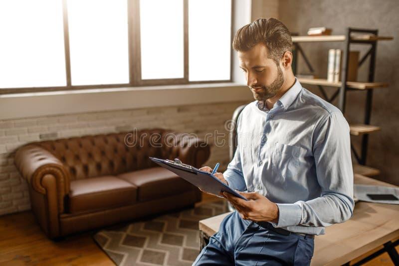 Den unga stiliga affärsmannen sitter på tabellen och blick på legitimationshandlingar i hans eget kontor Han läste dokument Funde royaltyfri bild