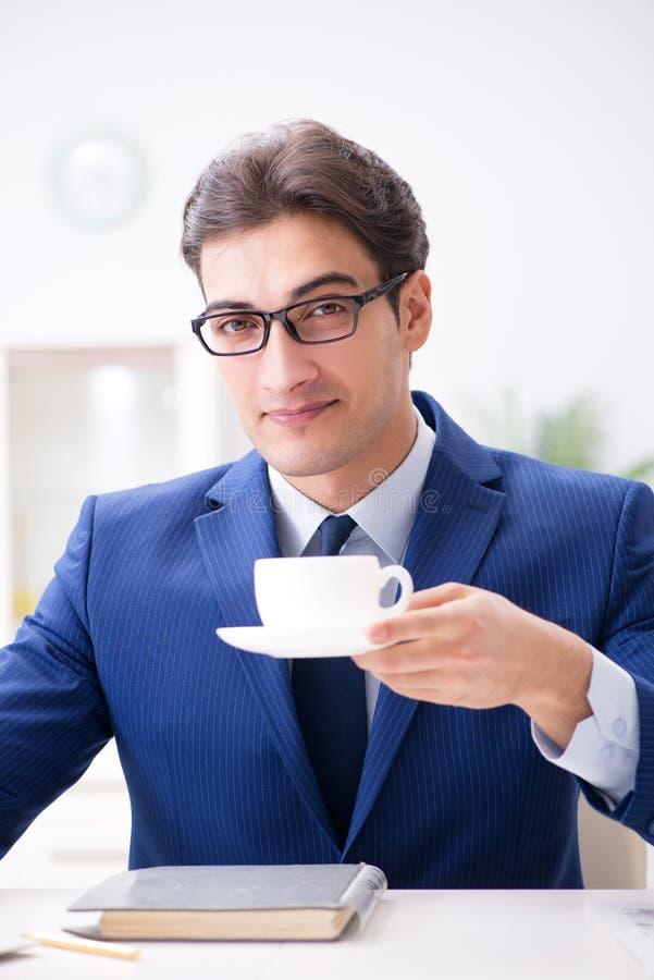 Den unga stiliga affärsmannen som dricker kaffe i kontoret royaltyfri fotografi