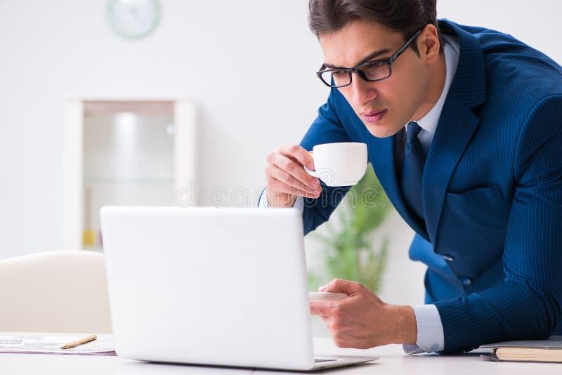 Den unga stiliga affärsmannen som dricker kaffe i kontoret arkivbilder