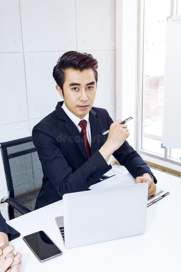 Den unga stiliga affärsmannen som ler och, ilar med pennan och bärbara datorn fotografering för bildbyråer