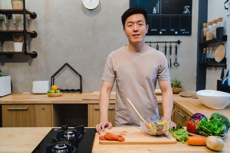Den unga stiliga asiatiska mannen förbereder salladmat och matlagning i köket royaltyfri foto