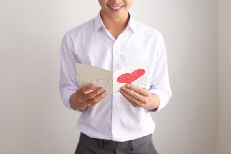 Den unga stiliga asiatiska mannen läser hälsningkortet med hjärtaform på vit bakgrund royaltyfri foto