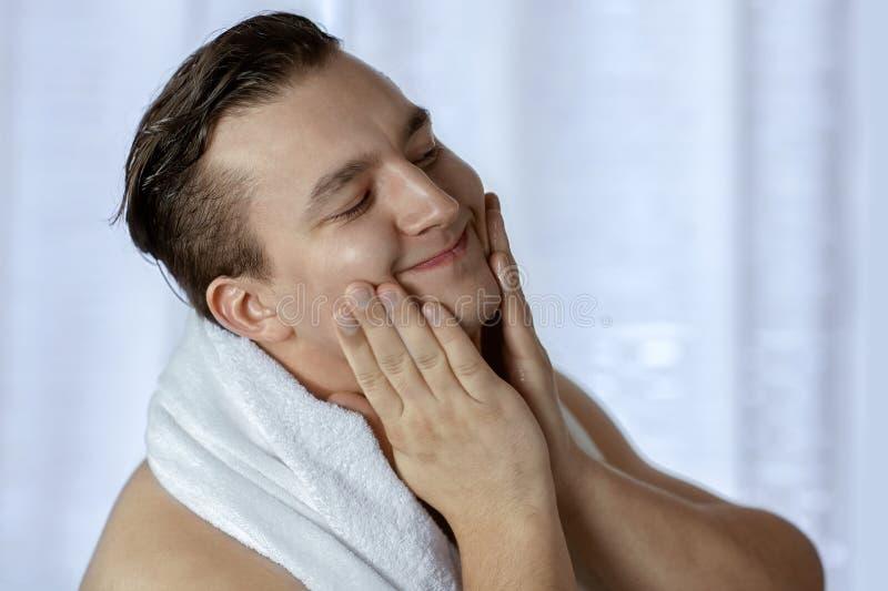 Den unga stiliga caucasian mannen klappade hans kinder, når han har rakat, handduk på skuldror Att bry sig framsidan med kräm ell royaltyfri foto