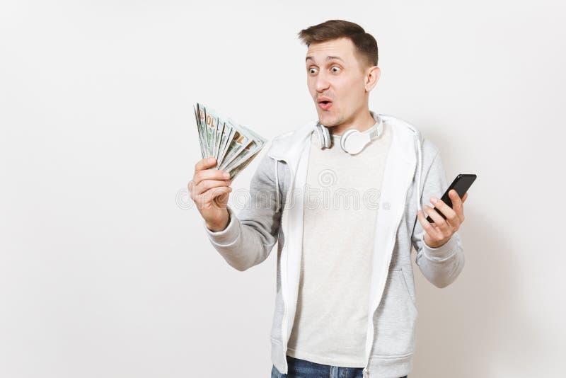 Den unga stiliga förvånade studenten i t-skjorta och ljus tröja med hörlurar runt om hals rymmer dollarräkningar och royaltyfri bild