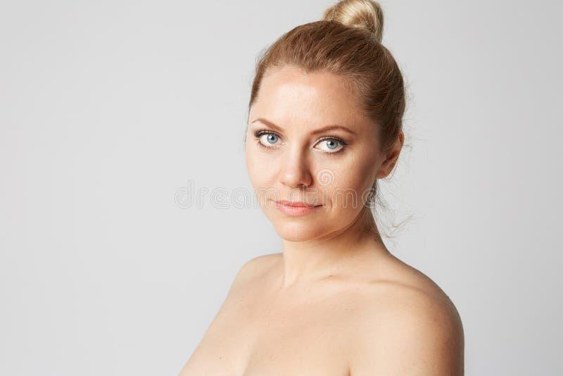 Den unga stiliga flickan med blont hår fixade bakom, stora ögon, tjocka ögonbryn och nakna skuldror som ler på grå färger arkivfoton