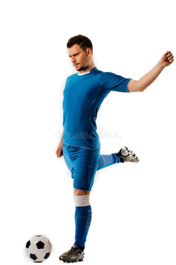 Den unga stiliga fotbollsspelaren rymmer att sparka fotbollbollen som poserar på vit isolerad bakgrund royaltyfri bild