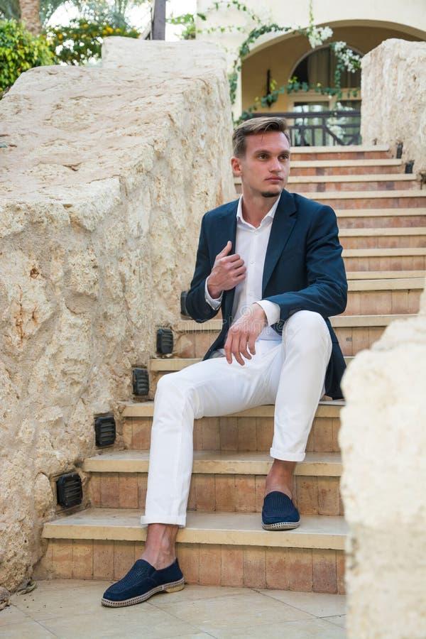 Den unga stiliga grabben i en dräkt och en vit byxa sitter på trappan arkivfoton