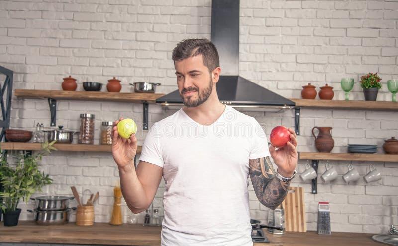 Den unga stiliga grabben rymmer ett grönt äpple i en hand, och det röda äpplet på begagnat, försöker han att välja royaltyfria foton
