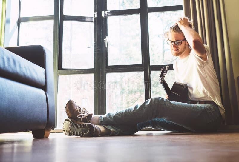 Den unga stiliga grabben sitter på golviat hem och lekar på gitarren royaltyfria foton