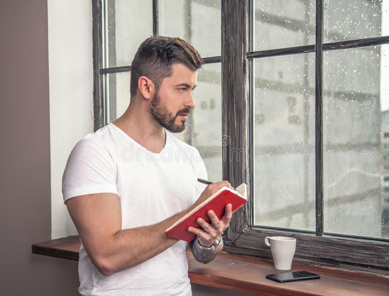 Den unga stiliga grabben står vid fönstret med en kopp för att gå kaffe som rymmer kvarteranmärkningen i hans hand och gör att tä royaltyfria foton