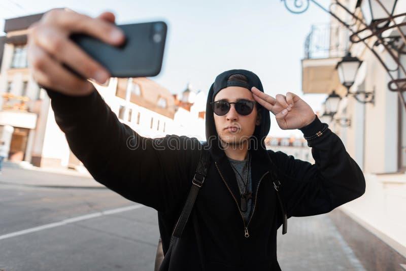 Den unga stiliga hipstermannen i trendig svart kläder i ett lock i solglasögon poserar och gör en selfie på en mobiltelefon royaltyfri fotografi