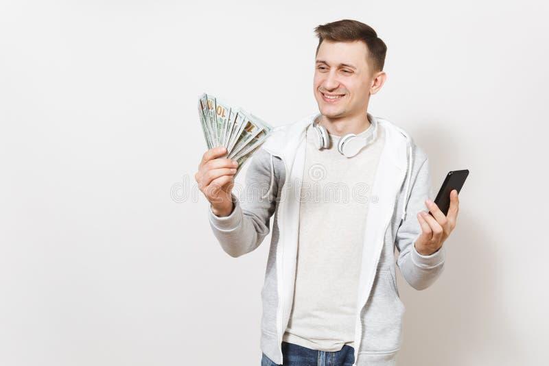 Den unga stiliga le mannen i t-skjorta och ljus tröja med hörlurar runt om hals rymmer packen av dollar, kassa royaltyfria foton