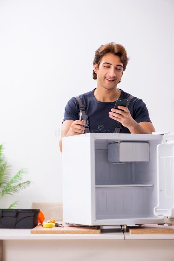 Den unga stiliga leverant?ren som reparerar kylen royaltyfri foto