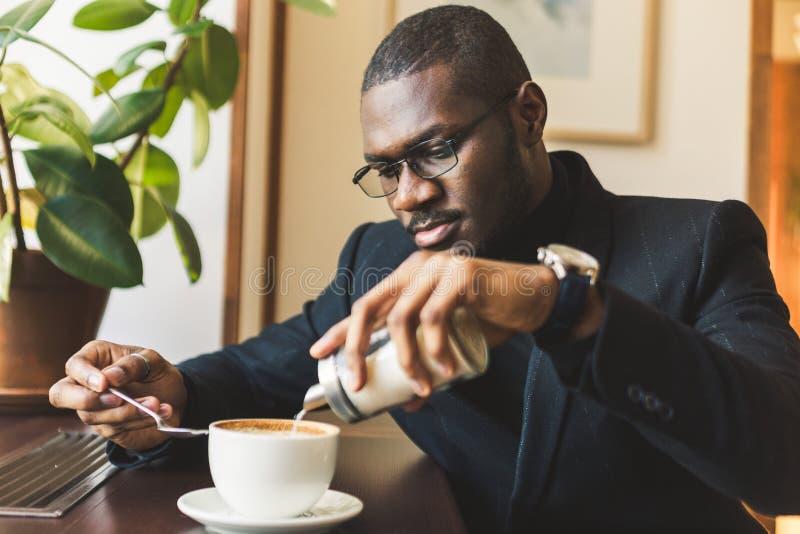 Den unga stiliga m?rkhyade aff?rsmannen dricker kaffe i ett kaf? royaltyfria bilder