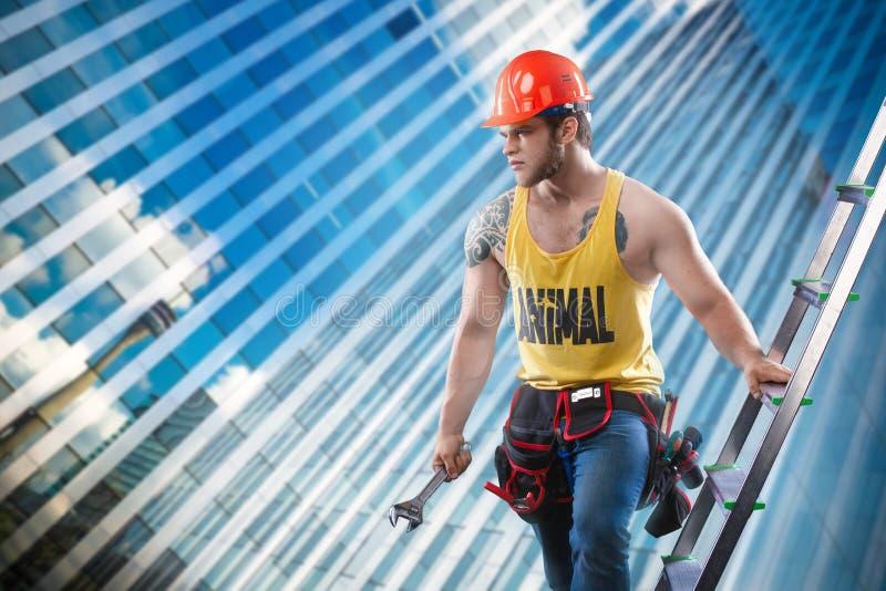 Den unga stiliga macho manbyggmästaren med den sexiga muskulösa idrotts- starka kroppen i orange hård hatt- eller hjälmhåll rycke fotografering för bildbyråer