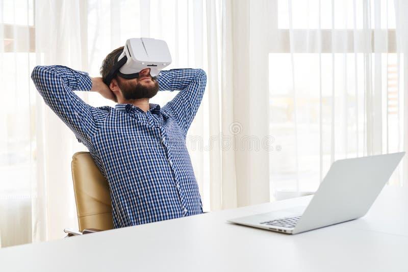 Den unga stiliga mannen är avslappnande i faktiska exponeringsglas 3d arkivfoto