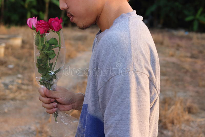 Den unga stiliga mannen är hållen och luktar en härlig bukett av röda rosor i hans hand han är väntanflickvännen Förälskelse och  arkivfoton