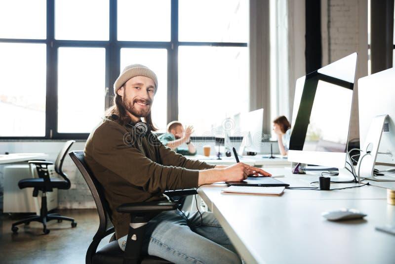 Den unga stiliga mannen arbetar i regeringsställning genom att använda datoren arkivbild