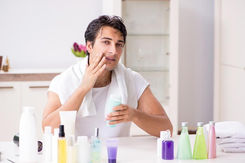 Den unga stiliga mannen i badrummet i hygienbegrepp royaltyfri fotografi