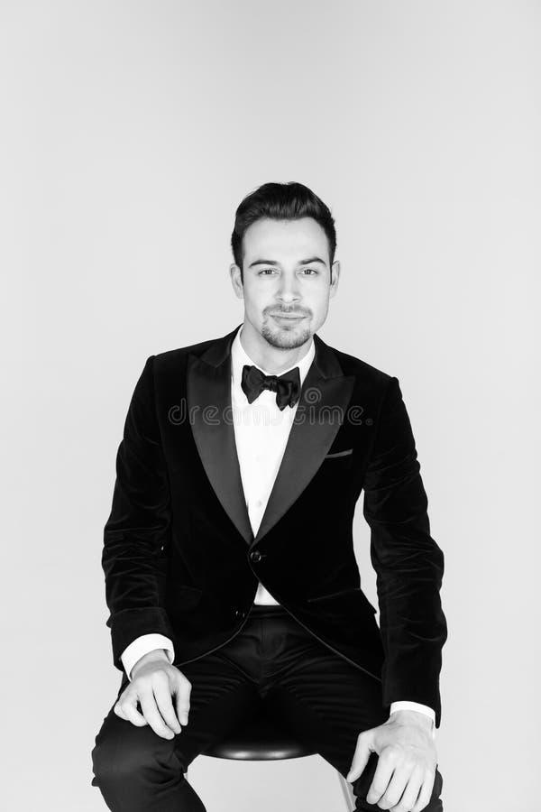 Den unga stiliga mannen i en smoking, ett sammanträde och se kom fotografering för bildbyråer