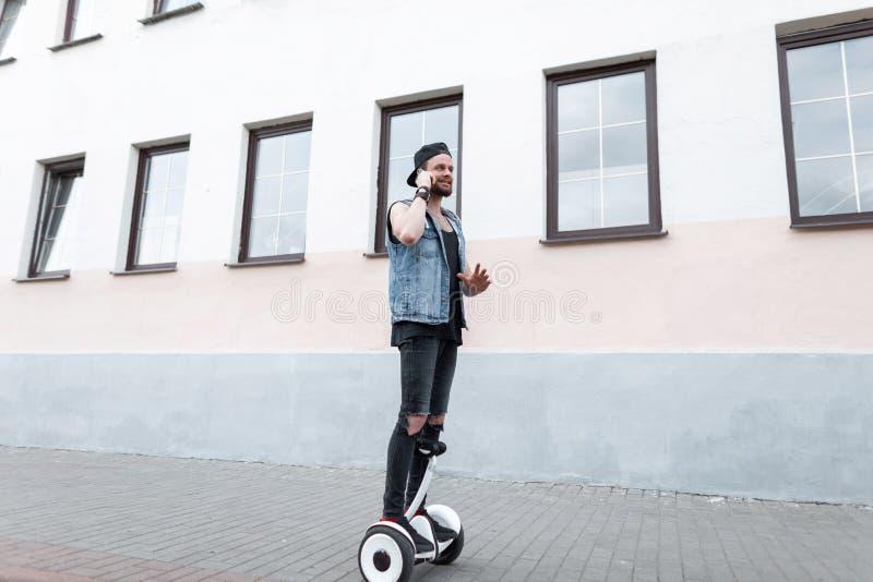 Den unga stiliga mannen i riven sönder svart jeans i en grov bomullstvill tilldelar ett lock i enskjorta i gymnastikskor på en ho arkivbilder