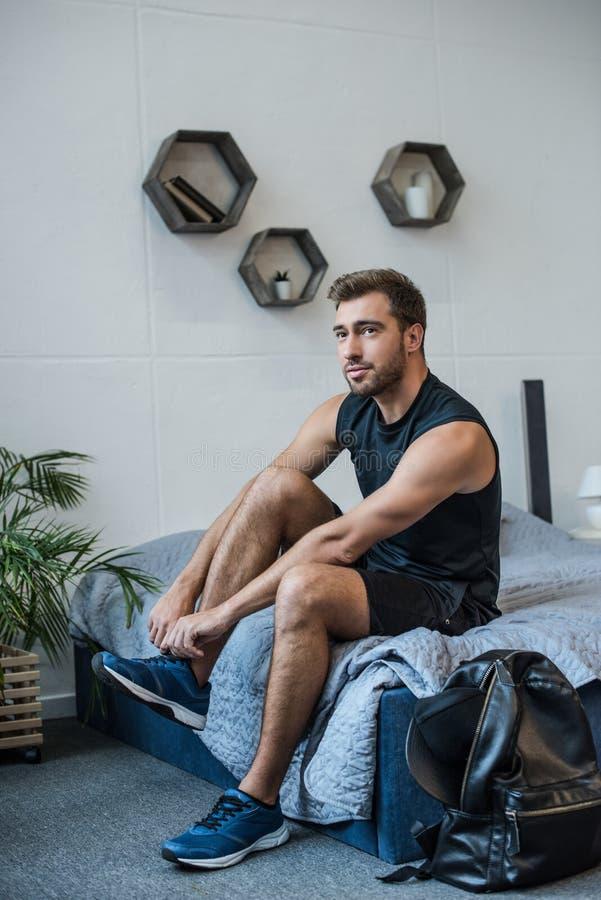 Den unga stiliga mannen, i sportswearsammanträde på säng och band, snör åt av hans royaltyfri fotografi