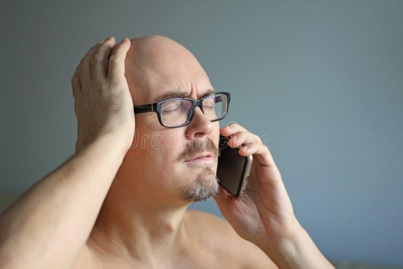 Den unga stiliga mannen i svarta exponeringsglas talar på telefonen och förvånas Stora problem, dåliga nyheter closeup isolerad m royaltyfri foto