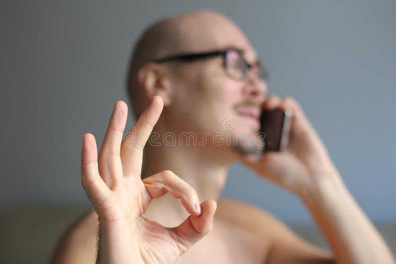 Den unga stiliga mannen i svarta exponeringsglas talar på telefonen Positiv nyheterna Stående av ett manslut upp En man visar all arkivfoto