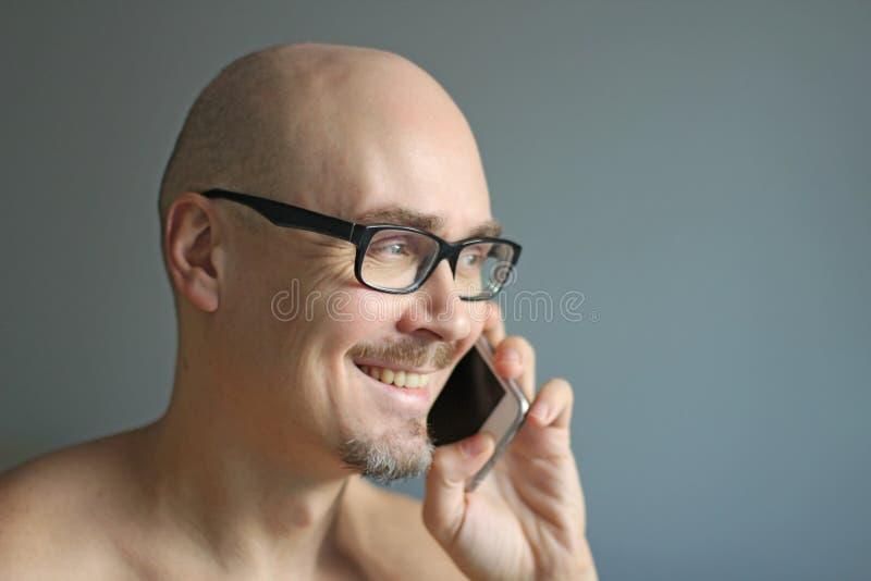 Den unga stiliga mannen i svarta exponeringsglas talar på telefonen som ler closeup isolerad manstående Chef kontorsarbetare som  arkivbild
