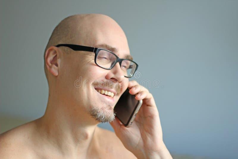 Den unga stiliga mannen i svarta exponeringsglas talar på telefonen som ler closeup isolerad manstående Chef kontorsarbetare som  arkivfoton