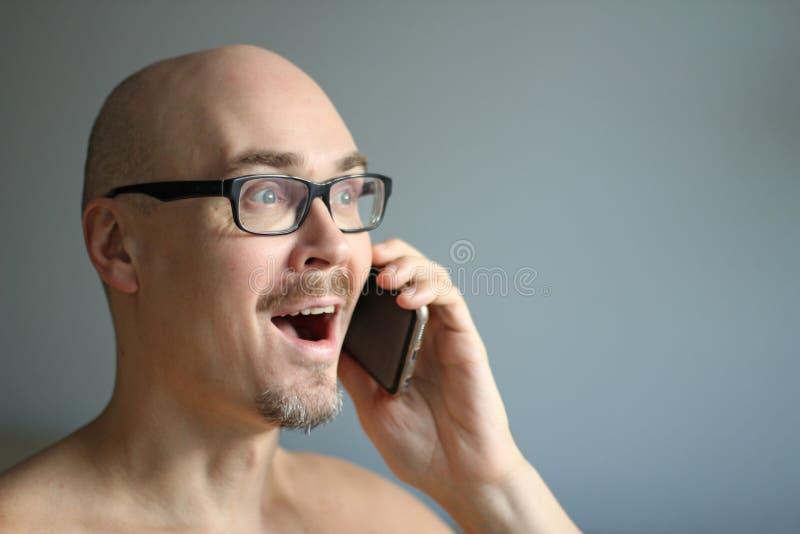 Den unga stiliga mannen i svarta exponeringsglas talar på telefonen som ler closeup isolerad manstående Chef kontorsarbetare som  royaltyfri foto