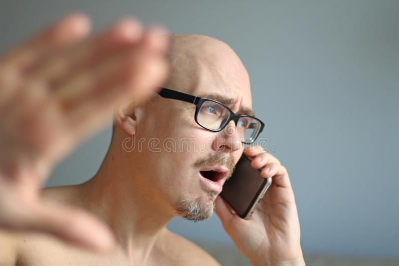 Den unga stiliga mannen i svarta exponeringsglas talar på telefonen Stora problem, skandal, dåliga nyheter closeup isolerad manst royaltyfria foton