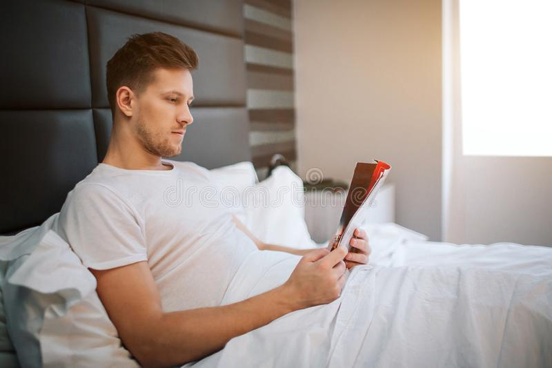 Den unga stiliga mannen läste in sovrummet koncentrerat Dagsljus Han täckte med den vita filten fotografering för bildbyråer