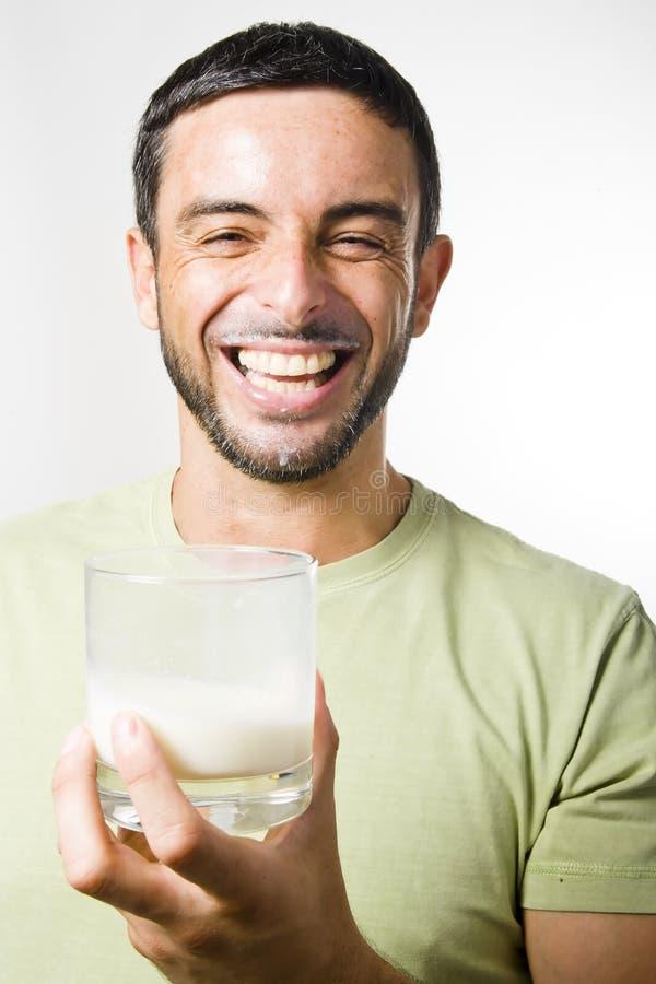 Den unga stiliga mannen med att dricka för skägg mjölkar arkivbild