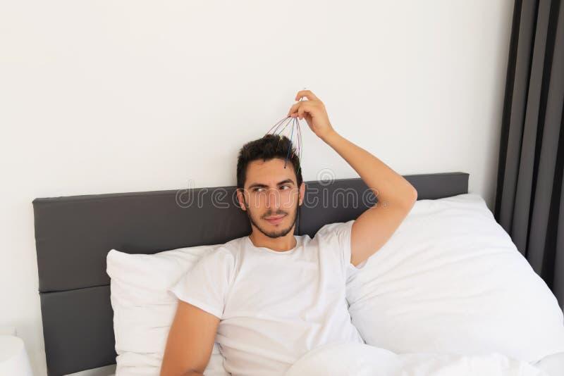 Den unga stiliga mannen med ett skägg sitter i hans säng royaltyfri foto