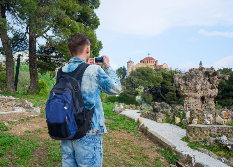 Den unga stiliga mannen som tar bilder på en smartphone av, fördärvar i pasha'sens trädgårdar och av kyrkan St Paul i i Anoen arkivbild