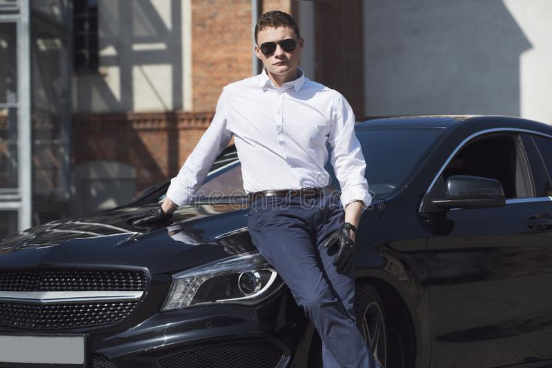 Den unga stiliga mannen står på en svart bil på bakgrunden av en stadsbyggnad fotografering för bildbyråer