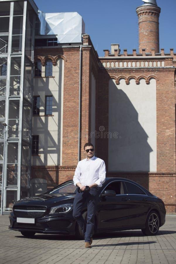 Den unga stiliga mannen står på en svart bil på bakgrunden av en stadsbyggnad royaltyfri foto