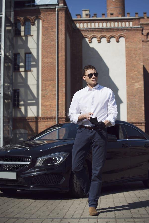 Den unga stiliga mannen står på en svart bil på bakgrunden av en stadsbyggnad royaltyfria bilder