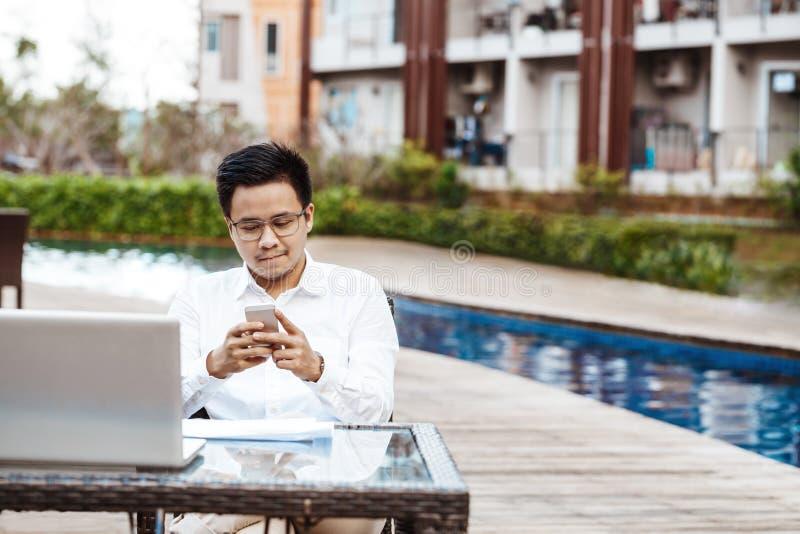 Den unga stiliga mannen tycker om att shoppa direktanslutet på mobiltelefonen med CR royaltyfri foto