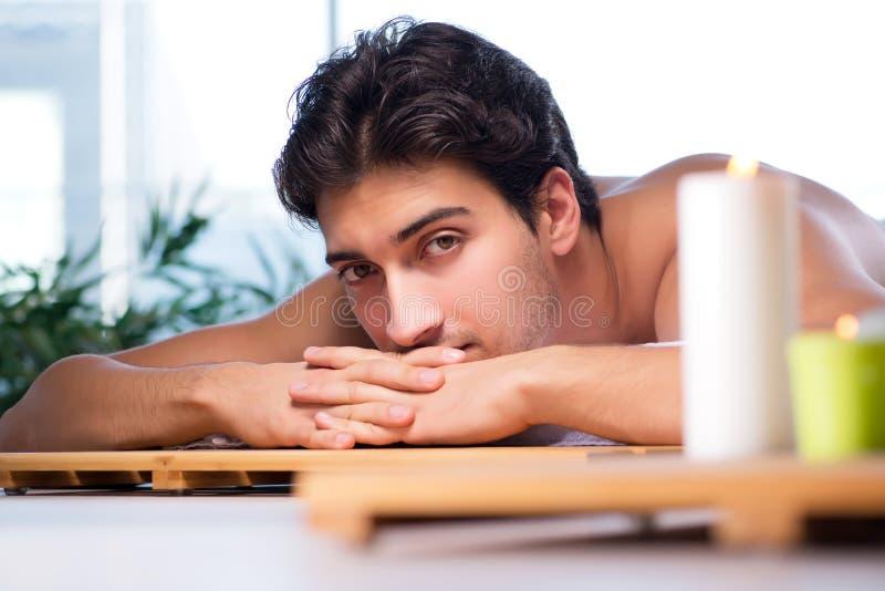 Den unga stiliga mannen under brunnsorttillvägagångssätt royaltyfri bild