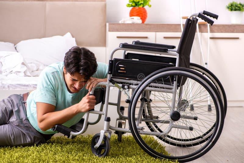Den unga stiliga rörelsehindrade mannen som hemma återställer royaltyfri bild