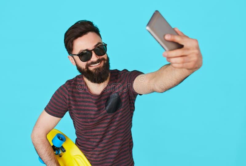 Den unga stiliga skäggiga hipstermannen gör selfie arkivfoto