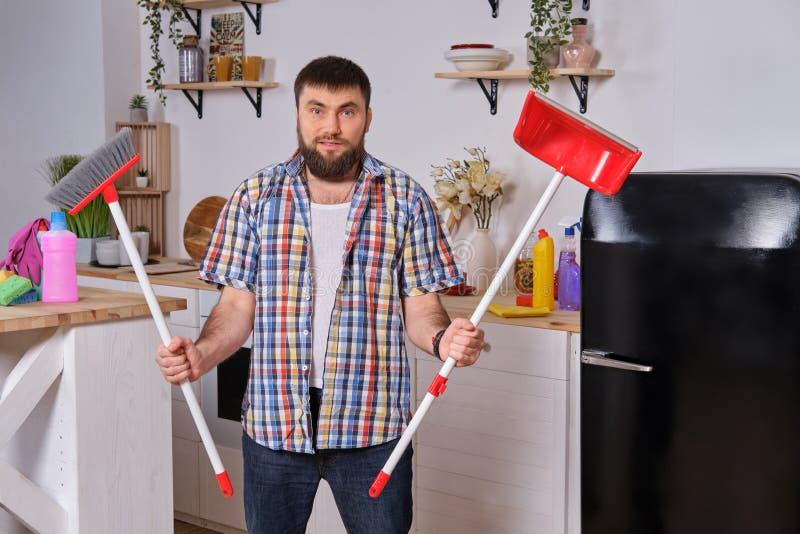 Den unga stiliga skäggiga mannen i köket, bärande rutig skjorta, försöker att handla med en sopskyffel och en kvast fotografering för bildbyråer
