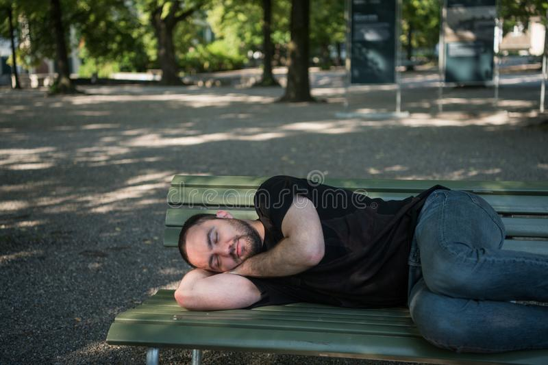 Den unga stiliga skäggiga mannen sover på parkerar bänken royaltyfria bilder