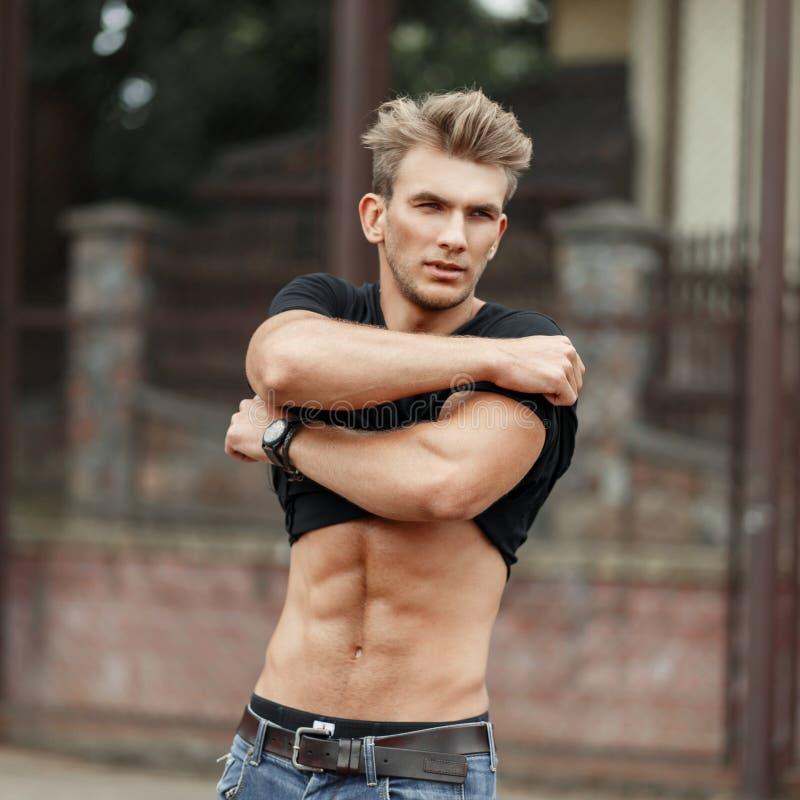 Den unga stiliga sportmodellmannen med en sund kropp tar royaltyfri bild