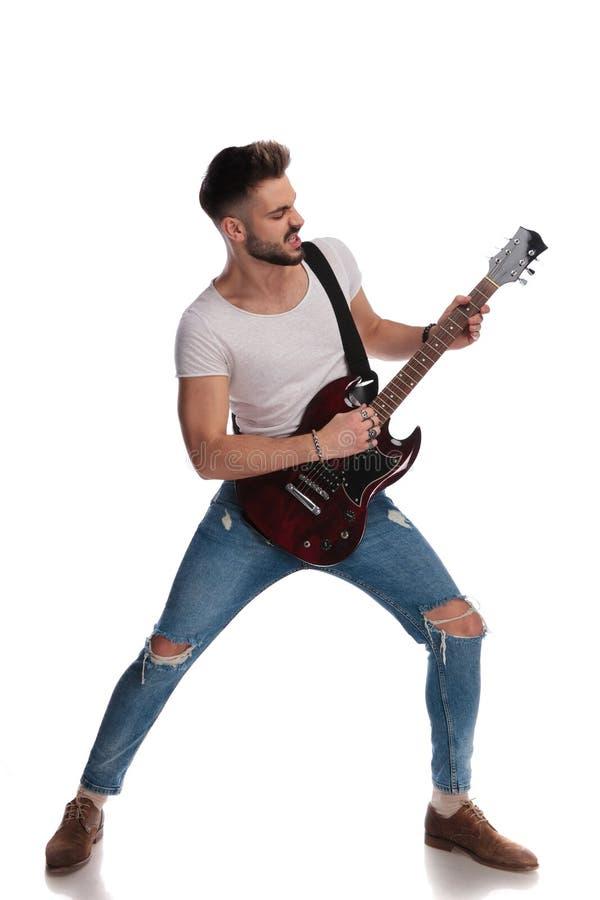 Den unga stjärnan som utför på en elkraft, vaggar gitarren fotografering för bildbyråer